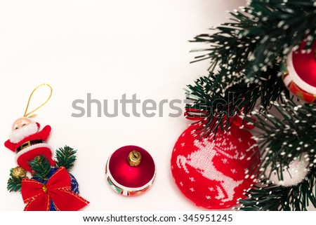 frame for text of Christmas toys on green fir branch namely big red ball with Christmas reindeer and also red ribbon, garland and toy Santa Clause - stock photo