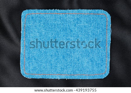 Frame for the text from a blue jeans fabric with the stitched lines of an orange thread, on a black silk - stock photo