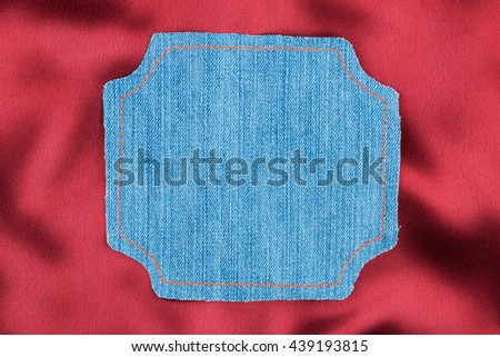Frame for the text from a blue jeans fabric with the stitched lines of an orange thread, on a red silk - stock photo