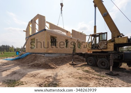 Frame house construction. View on new building with crane - stock photo
