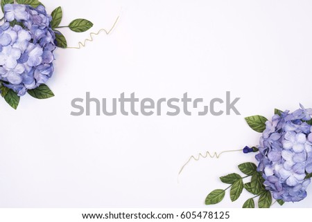 Frame made of blue hydrangea, green leaves, branches on white background. Flat lay, top view. Wedding's background