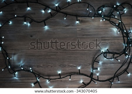 Frame made of christmas lights on a wooden surface - stock photo