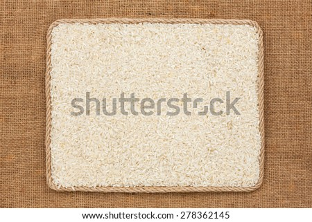 Frame made of rope with rice grains on sackcloth, as background, texture