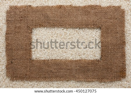 Frame made of rough burlap lies on rice grains, as background - stock photo