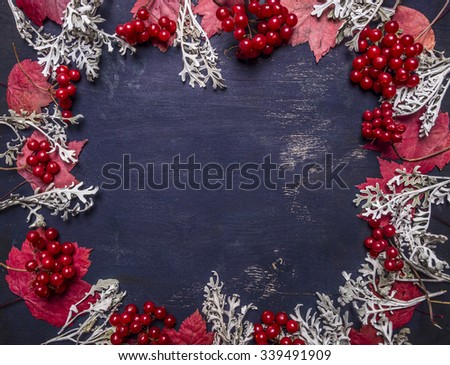 Frame of autumn decorations, berries and leaves  place for text,frame on wooden rustic background top view