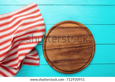 Frame Of Brown Round Cutting Board And Red Striped Tablecloth. Blue Wooden  Background In The