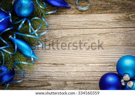 Frame of Christmas fir tree branch with blue Christmas balls on an old wooden board, top view. Copy space for text.