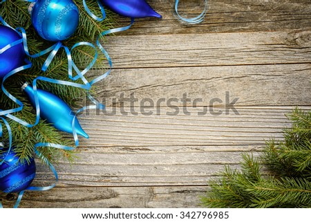 Frame of Christmas fir tree branches with blue ornaments on an old wooden board, copy space for text, top view.