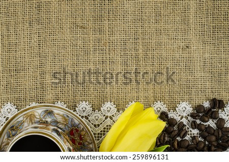 Frame of coffee cup, yellow flower and coffee beans on linen background - stock photo