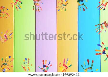 Frame of color hands print on wooden background - stock photo