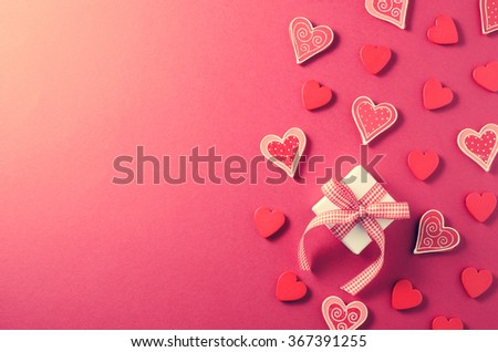 Frame of gift box and hearts on red background
