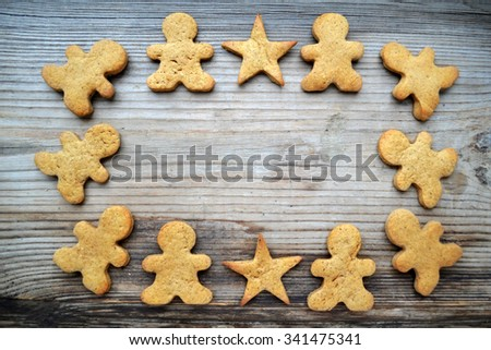 Frame of gingerbread cookies in shape of man on wooden table