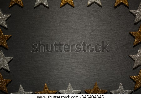Frame of golden and silver stars on slate texture background, christmas decoration. - stock photo