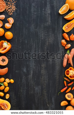 Frame of raw organic produce orange vegetables on dark rustic distressed background, part of a group