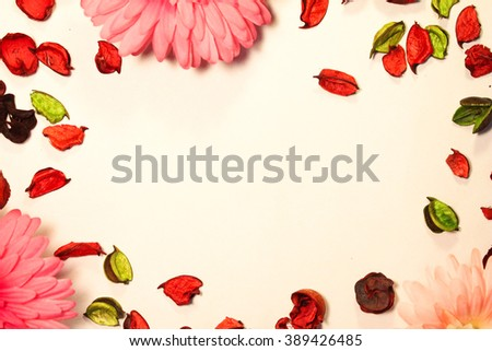 Frame of red flowers of chrysanthemum and dry red and green petals of roses. Top view. Flat lay. - stock photo