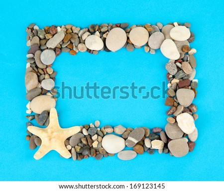 Frame of sea stones on color background - stock photo