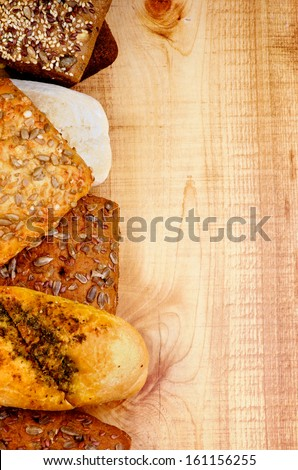 Frame of Sesame Seed Bun, Baguette, Whole Wheat Bread, Ciabatta and 7-Grain Bread closeup on Wooden background - stock photo