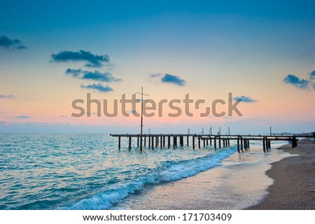 frame of the old pier on the beach at dawn - stock photo