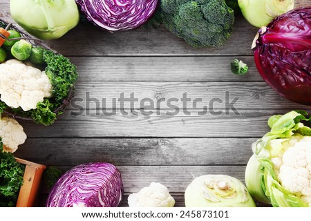 Frame of various brassica cabbage family varieties with cauliflower, kohlrabi, kale, cabbage and brussels sprouts over a rustic wooden background with copyspace - stock photo