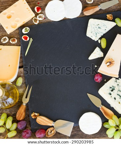 Frame of various types of cheese and appetizer on black cutting board with copy space, top view - stock photo