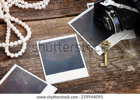 frame of vintage  photo camera with  pile of retro instant photos on wooden background - stock photo