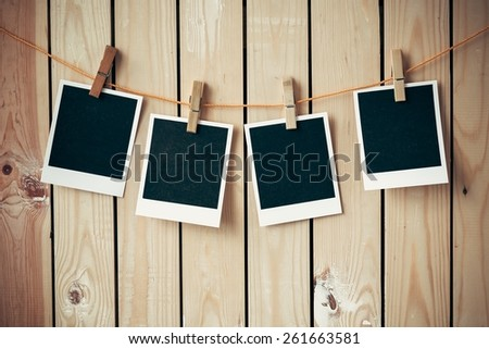 Frame. Old picture frame hanging on clothesline on wood background. - stock photo