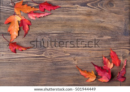 Frame with autumn leaves on wooden background, top view
