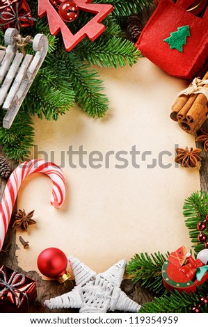 Frame with Christmas tree branches and vintage festive decorations on wooden background - stock photo