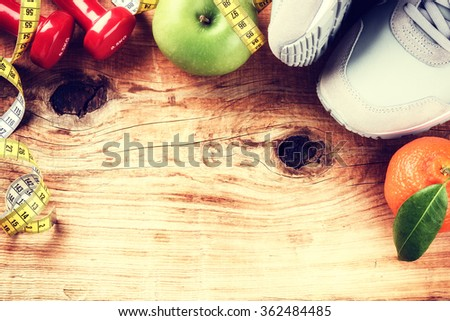 Frame with dumbbells, sneakers and fresh fruits. Fitness and diet concept with copy space  - stock photo