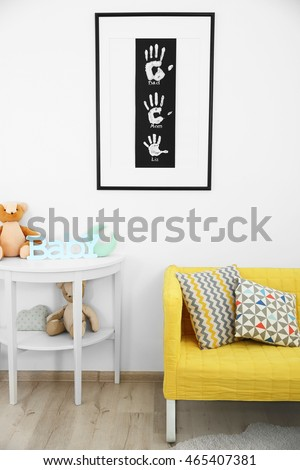 Frame with family hand prints on wall in room