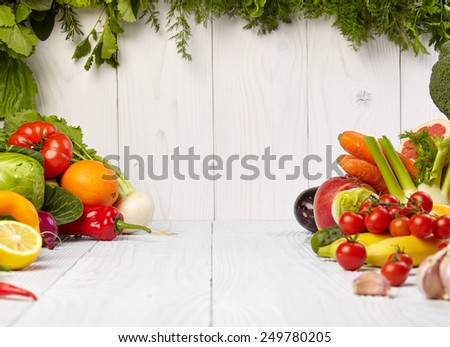 frame with fresh organic vegetables and fruits on wooden background - stock photo