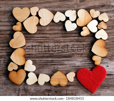 frame with hearts on a wooden background