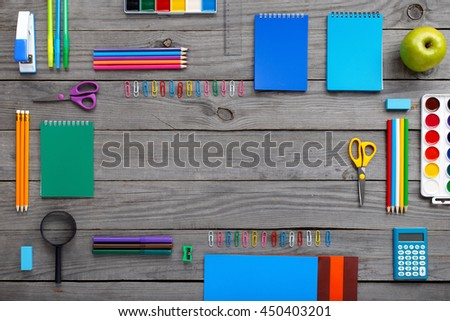 Frame with school supplies on a wooden table. Flat lay, top view - stock photo