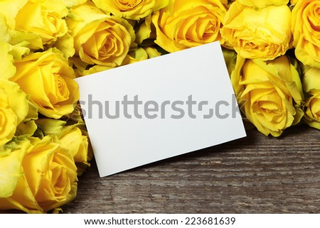 Frame with yellow roses on old wooden background - stock photo