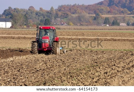 Framer ploughing with the tractor on the autumn fields.