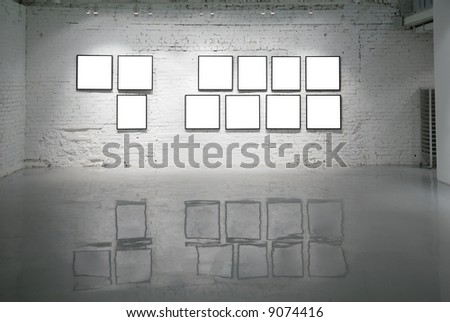 frames on white brick wall and reflections on floor - stock photo