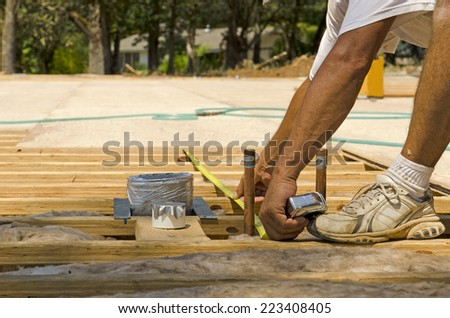 Framing contractor measuring for stubbed up domestic water and drain lines to install plywood subfloor to wood joist - stock photo