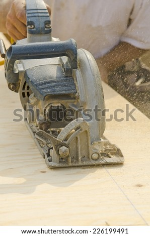 Framing contractor uses a circular had saw to cut and trim plywood sub floor panels on a new luxury custom residence - stock photo