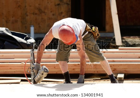 Framing contractor worker working on a small wall  on a new commercial residential development - stock photo