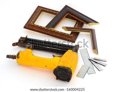 Framing tools. Kind of put a nail gun shot off the back of a wooden frame and the frame on the white background.  - stock photo
