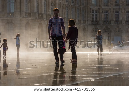 FRANCE, BORDEAUX - SEPTEMBER 20: People having fun in a mirror fountain in front of Place de la Bourse in Bordeaux, France on September 20, 2015