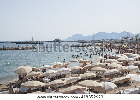 FRANCE, CANNES - AUGUST 6, 2013: A lot of people on the beach near the Palais des Festivals. - stock photo