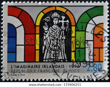 FRANCE - CIRCA 1996: A postage stamp printed in France shows a detail of a stained glass window of St. Patrick, Irish imaginary sample, circa 1996. - stock photo