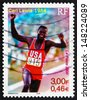 FRANCE - CIRCA 2000: a stamp printed in the France shows Carl Lewis Wins Four Olympic Gold Medals, 1984, circa 2000 - stock