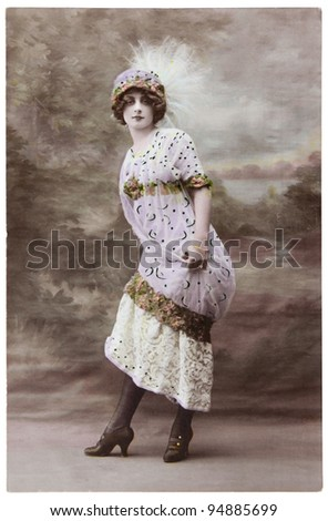 FRANCE - CIRCA 1906: a vintage postcard printed in France shows hand painted photograph of beautiful lady in fashion dress of 1906. Circa 1906. - stock photo