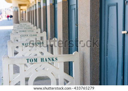 FRANCE, DEAUVILLE - SEPTEMBER 27: original beach closets with famous names on promenade Des Planches in Deauville, France on September 27, 2015 - stock photo