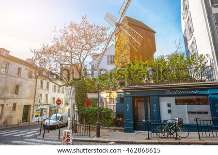 France. Paris. Moulin de la Galette. Streets of Montmartre in sunny autumn evening in backlit sunset sunbeam with vintage camera lense look.