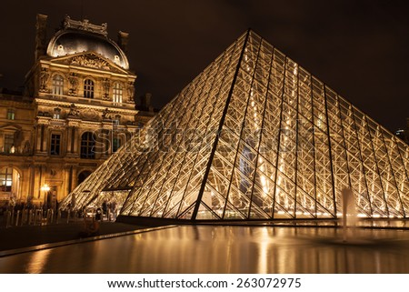 France, Paris - Nov 25, 2013: The Louvre Pyramid on November 25, 2013 in Paris, France. It serves as the main entrance to the Louvre Museum. Completed in 1989 it has become a landmark of Paris. - stock photo