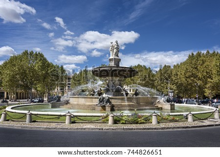 France, Provence, Aix-en-Provence - August 11: Street scene with  Fountaine de la Rotonde in the sun and blue cloudy sky, August 11, 2017
