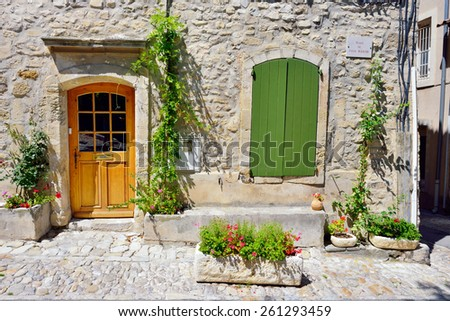 France, Provence. Small square in Vaison la Romaine - Place Du Vieux Marche. Typical medieval houses decorated with green plant and flowers in pots.  - stock photo